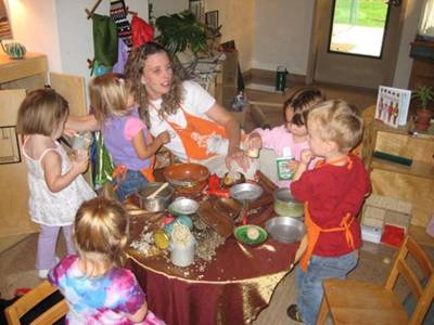 Children cooking with teacher