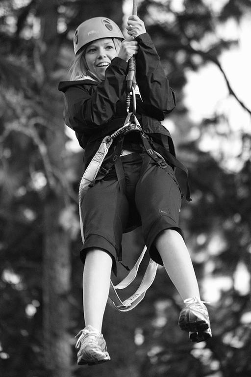 female student riding zipline