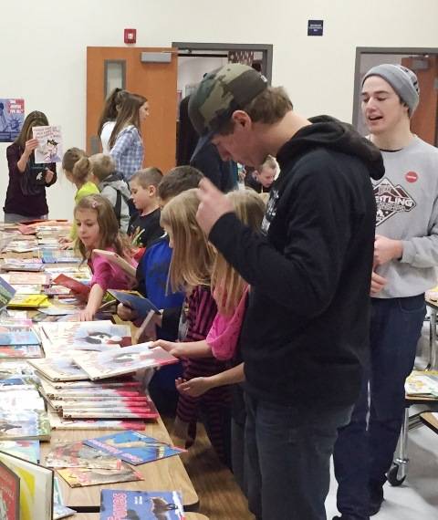 NIC wrestling team helps hand out books