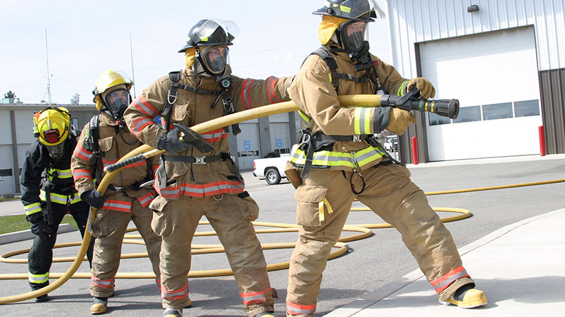 firefighter students aiming firehose
