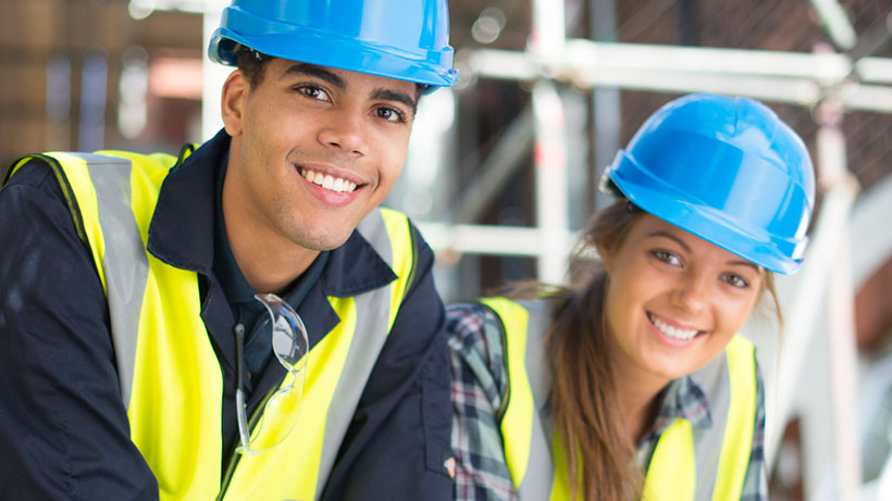 male and female students in hard hats smiling
