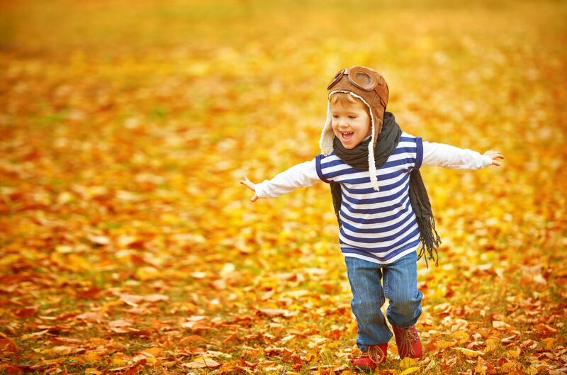 child running through leaves